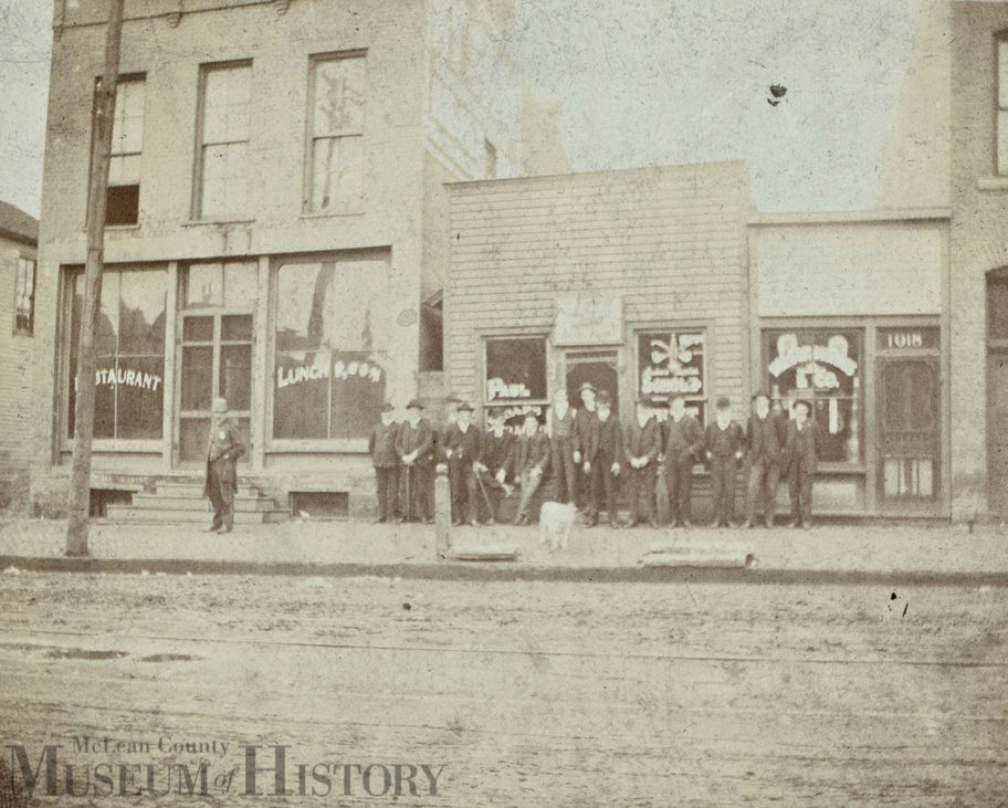 Boys and young men gather outside Paul Scholz cigar and tobacco shop, 1018 W. Washington St.