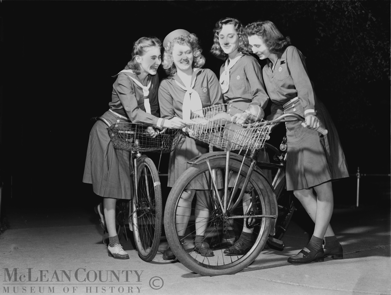 Seen here are Bloomington area Girl Scouts training as blackout and air raid messengers. From left to right: Charlotte Ratcliffe, Isabel Gottschalk, Kay Johnston, and Gloria Sampson.