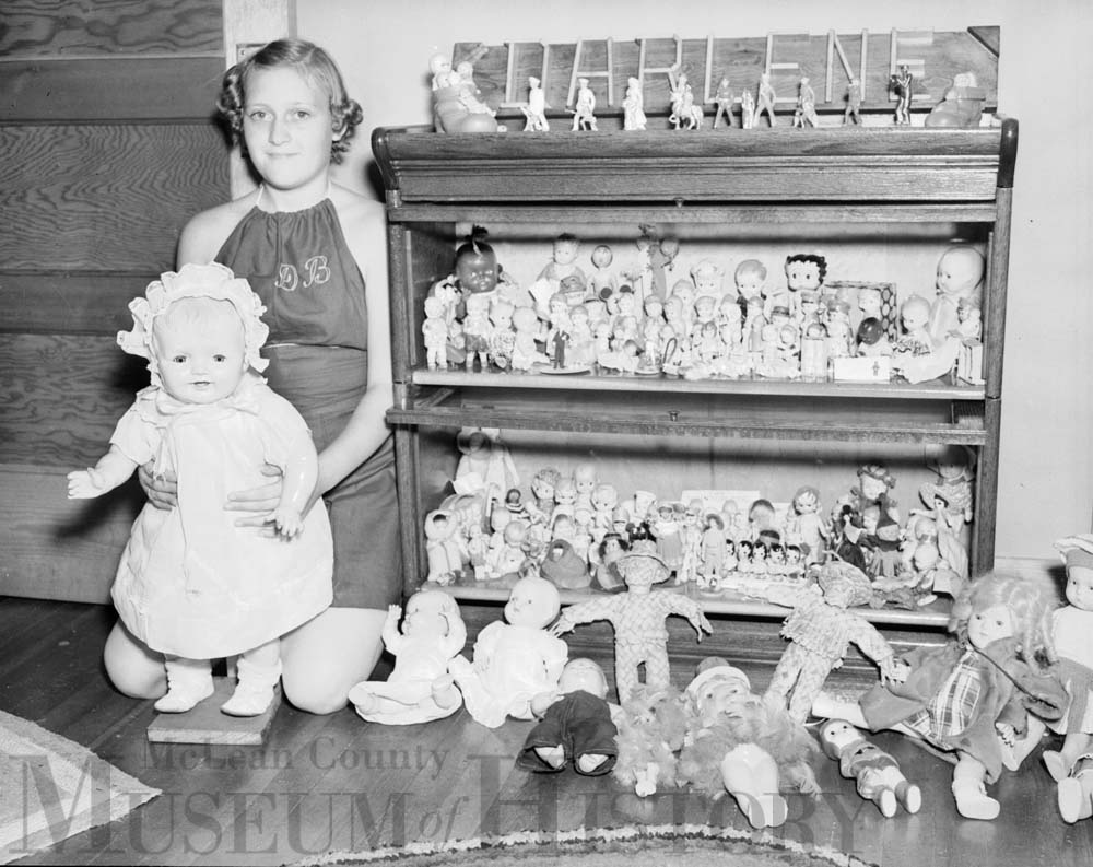 Young girl poses with doll collection, 1938.