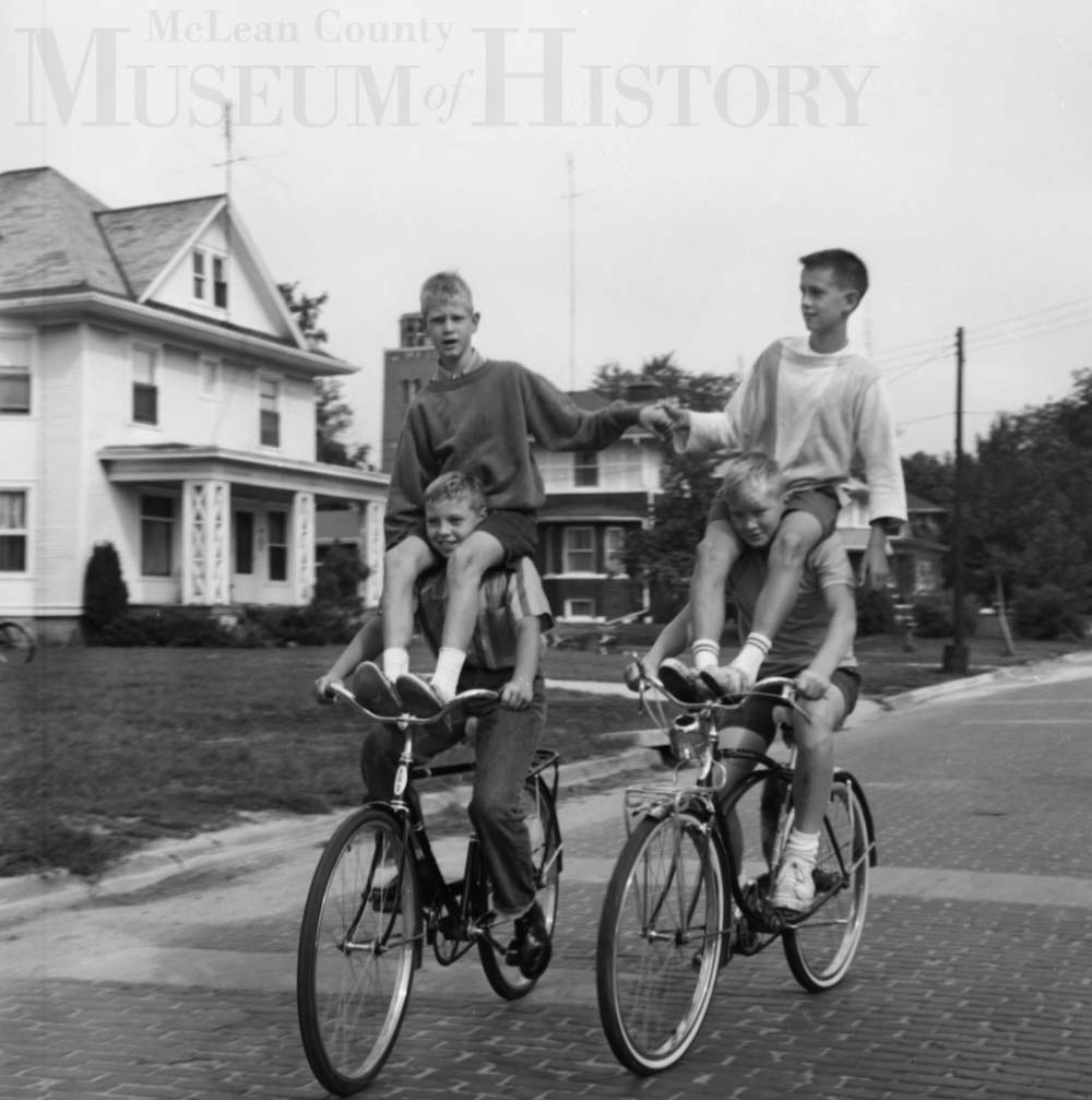 Four boys riding two bikes, 1963