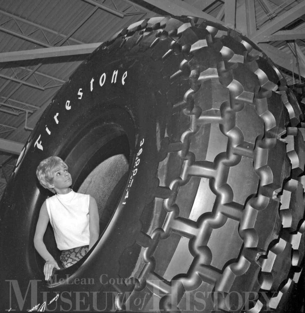 a woman is pictured standing in the middle of a gigantic approx 12 foot diameter firestone tire.