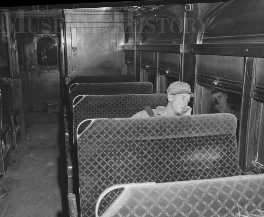 Man sitting in a train car, 1950.