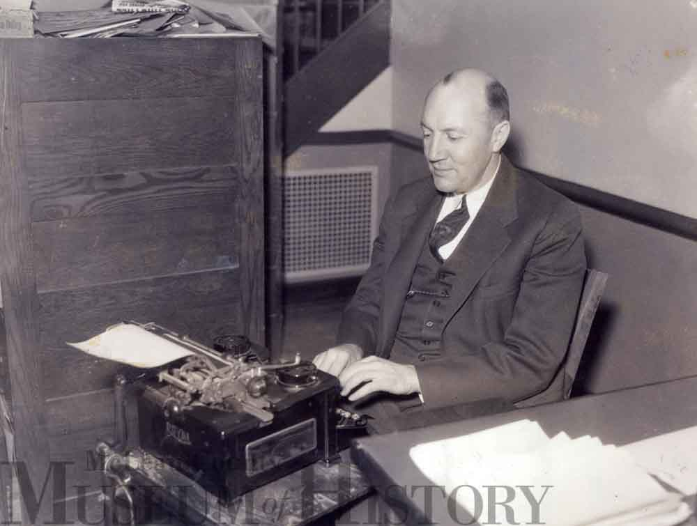 "Pantagraph sports editor Fred ""Brick"" Young sitting at a desk typing on a typewriter"