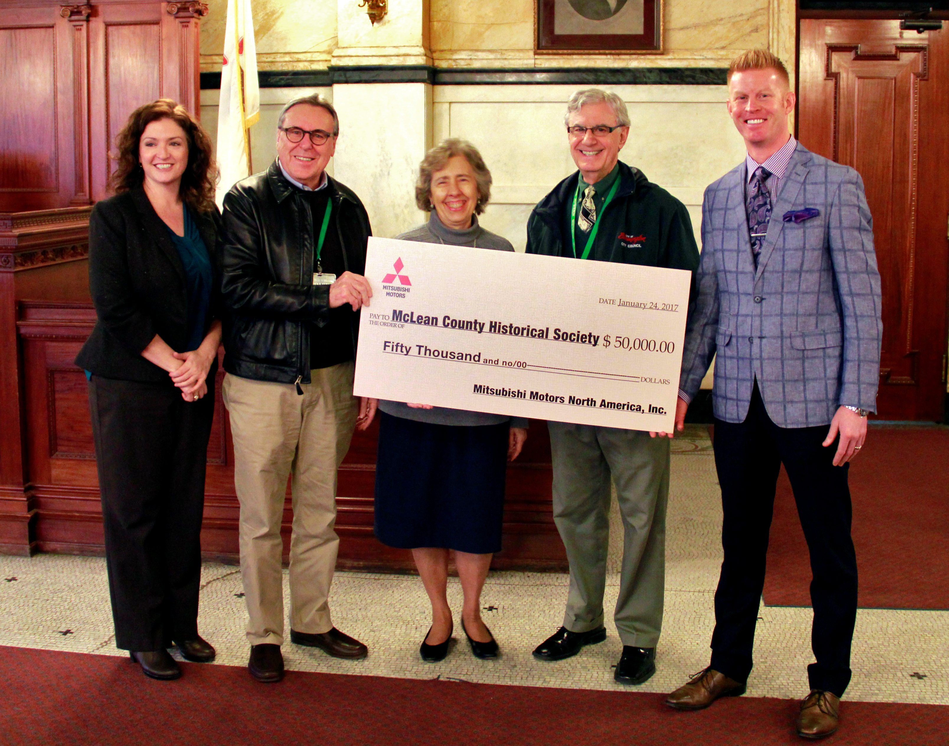 Ryan Gremore, general manager and operating partner of O'Brien Mitsubishi of Normal (far righ) presents a $50,000 donation to Museum board members and Museum Executive Director Beth Whisman.
