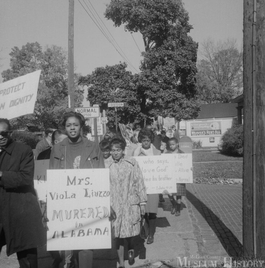 demonstrators from Illinois State University marched along Main Street to downtown Bloomington to protest the acquittal in Alabama of Ku Klux Klan gunman Collie Leroy Wilkins in the murder of Civil Rights Movement worker Viola Liuzzo.